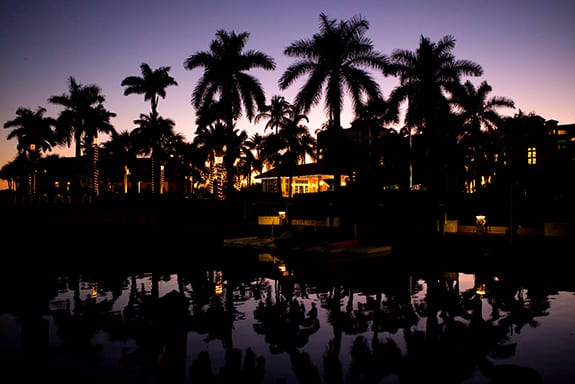 A canal-side Florida home is seen at night time as lights highlight nearby palm trees.