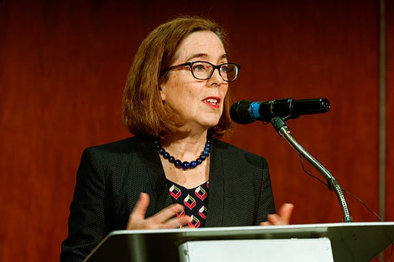 Oregon Governor Kate Brown speaks at a podium against a red wooden-paneled wall.