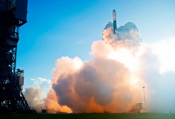 A Delta II rocket is engulfed in vapor as it begins to take off from the launch pad in Florida.