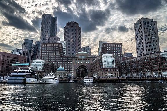 Boston Massachusetts is seen from the water in a cloudy and unsaturated light.