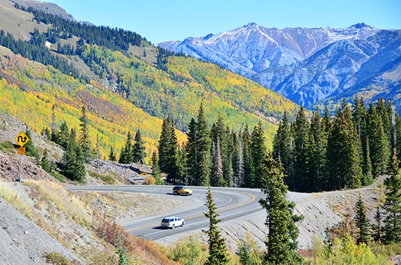 A picture-perfect Colorado serpentine road cuts through steep forested mountains against a clear blue sky.