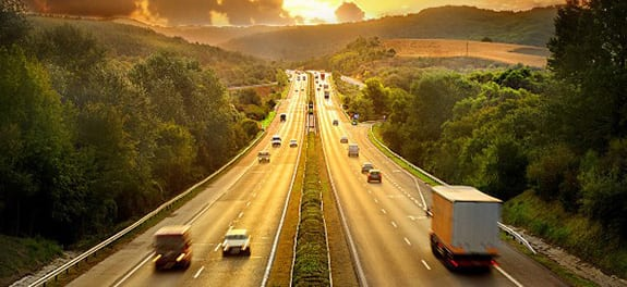 A split four-lane highway rises on a gentle hill to meet the horizon under a low golden yellow sun.