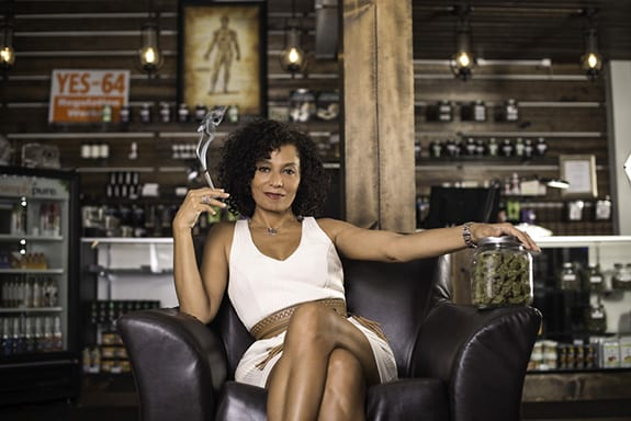 Entrepreneur Wanda James sits looking at the camera holding a lit joint in dispensary.